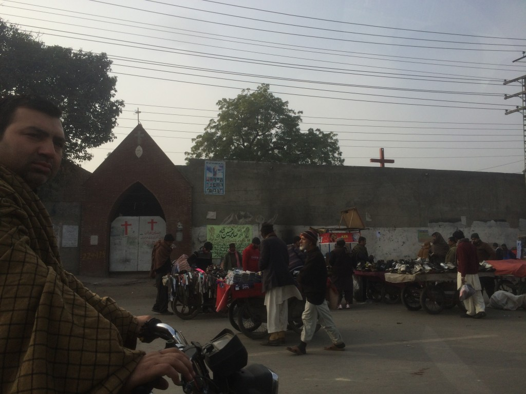 Juxtaposition of a Christian church near the Walled City behind a high security wall and the daily activities unfolding in front of it.